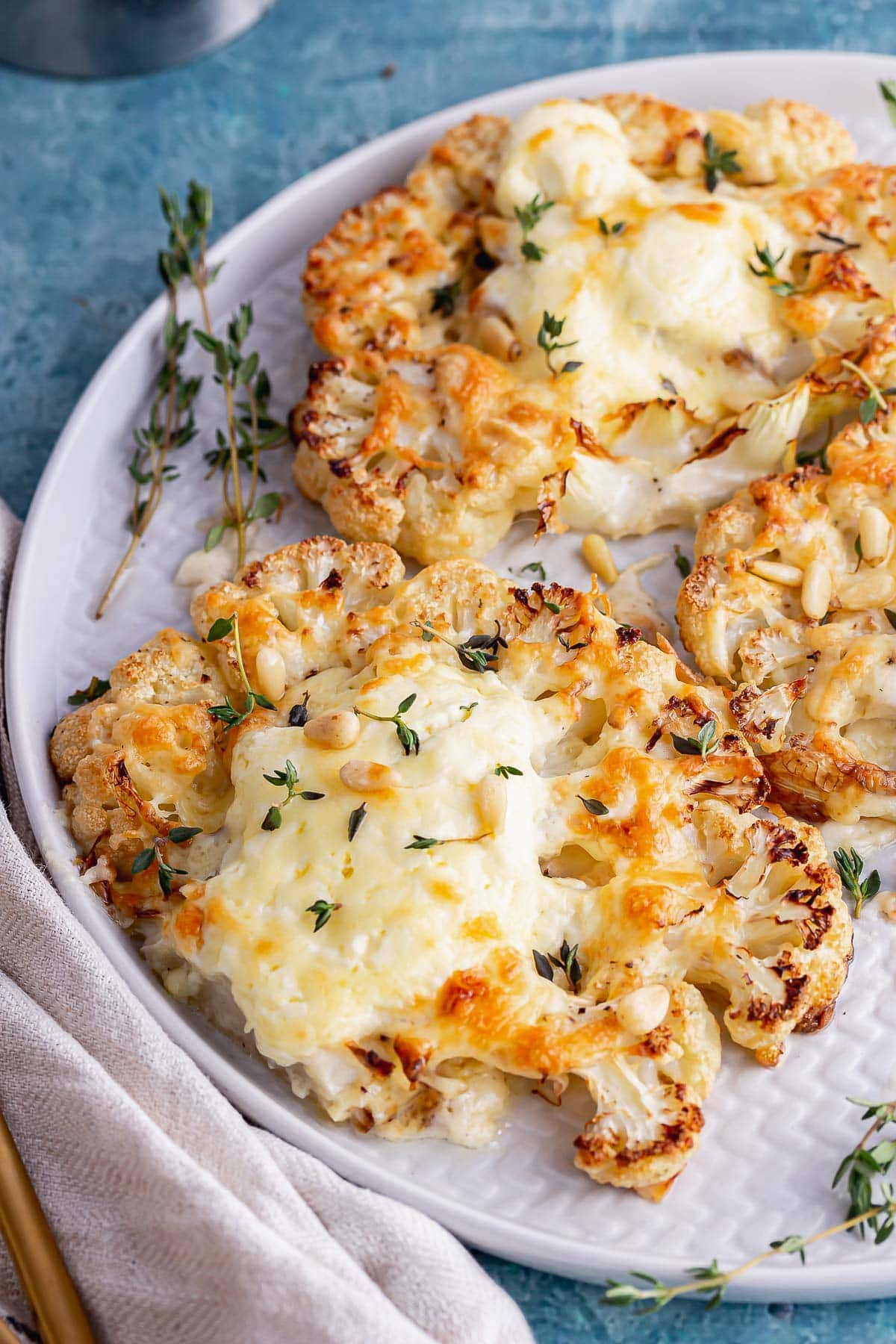 Plate of cheesy cauliflower with thyme on a grey plate