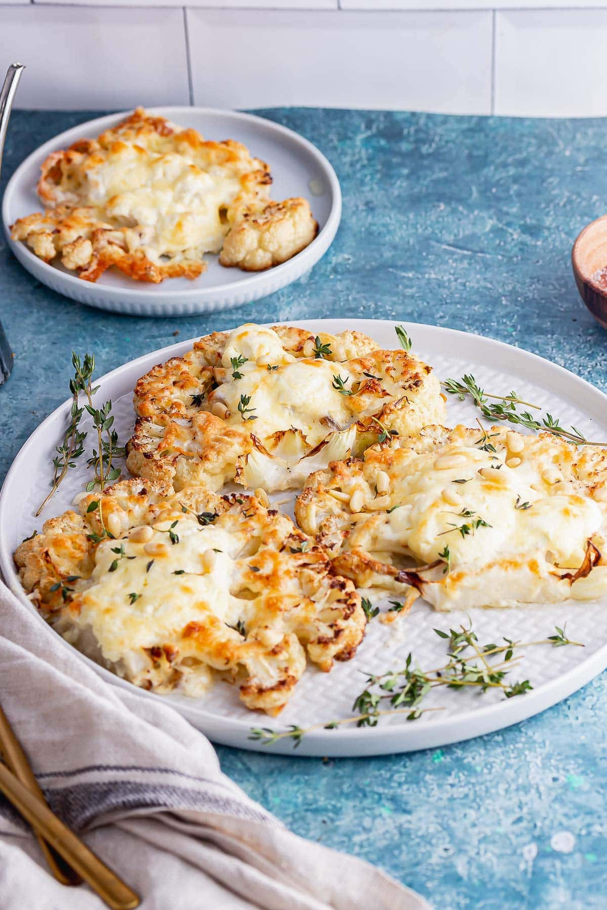 Plate of cauliflower steaks with cheese on a blue background