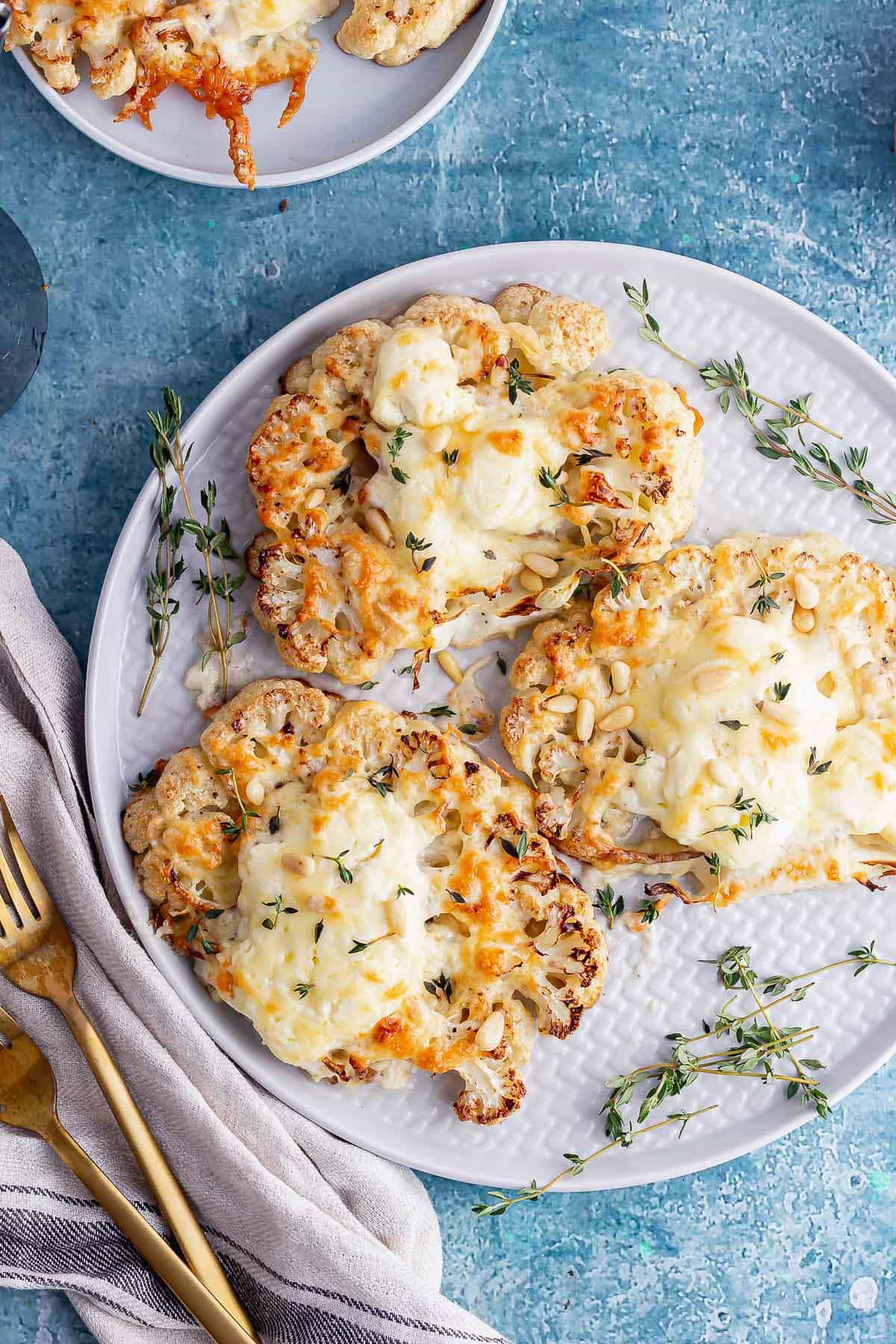 Cheesy cauliflower steak with cloth and gold fork