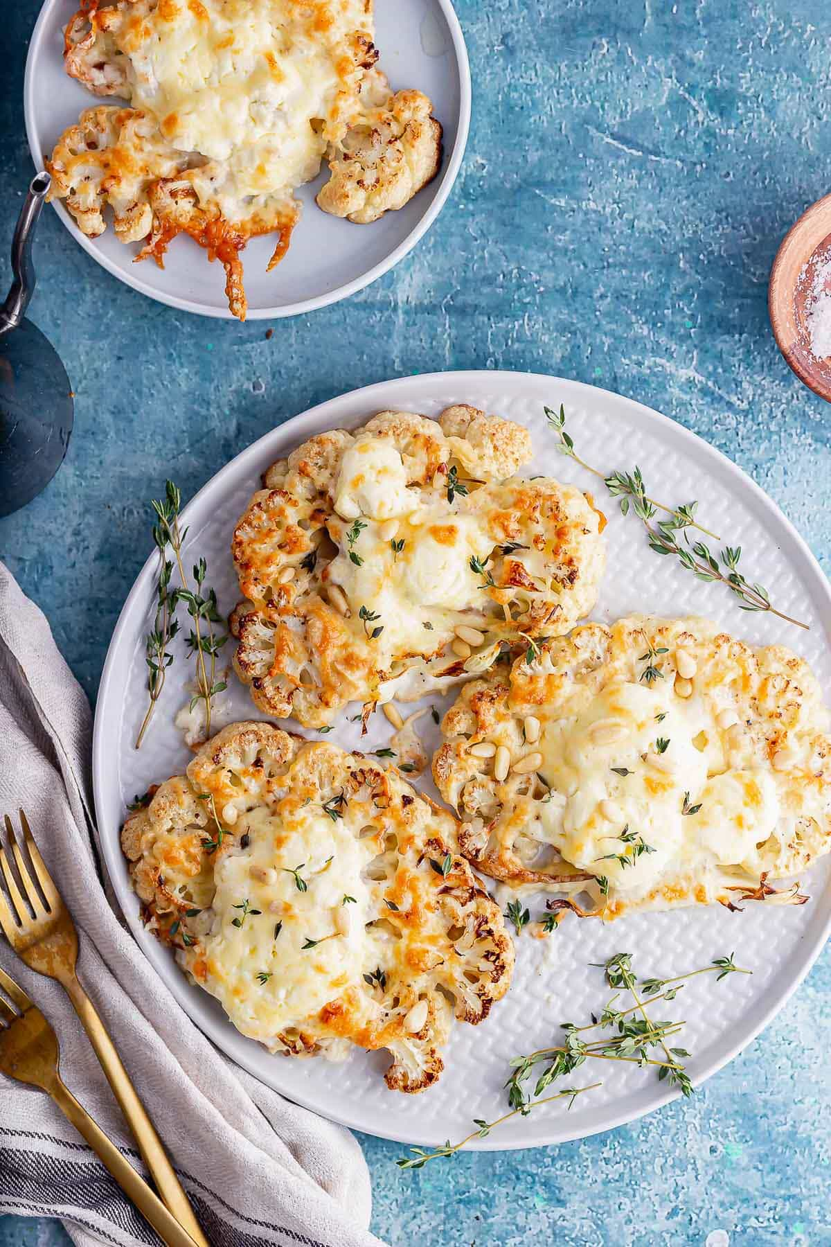 Overhead shot of cauliflower cheese steaks on a blue background