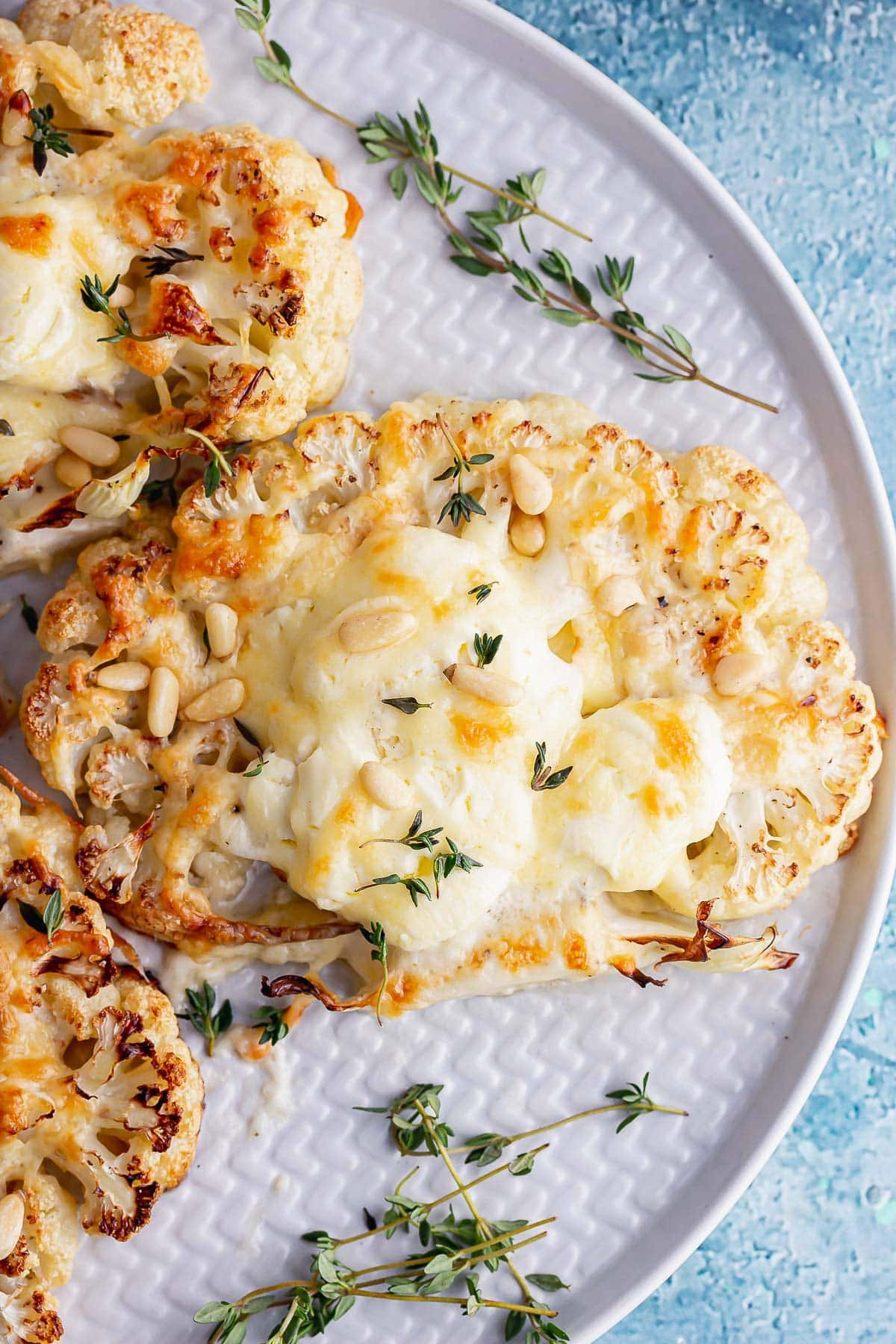 Overhead shot of a cheesy cauliflower steak with thyme sprigs