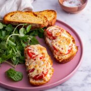 Pink plate of prawn sandwich with tomato on a marble surface