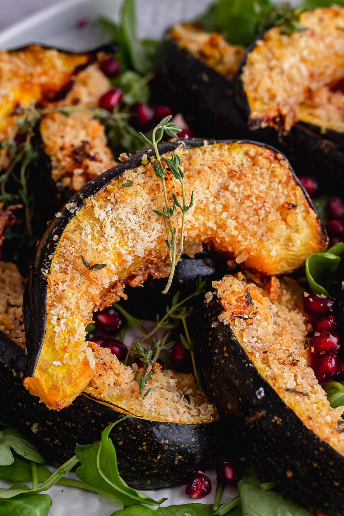 Close up of crispy roast squash with thyme and pomegranate