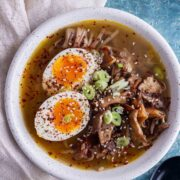 Overhead shot of mushroom miso soup with a boiled egg in a white bowl