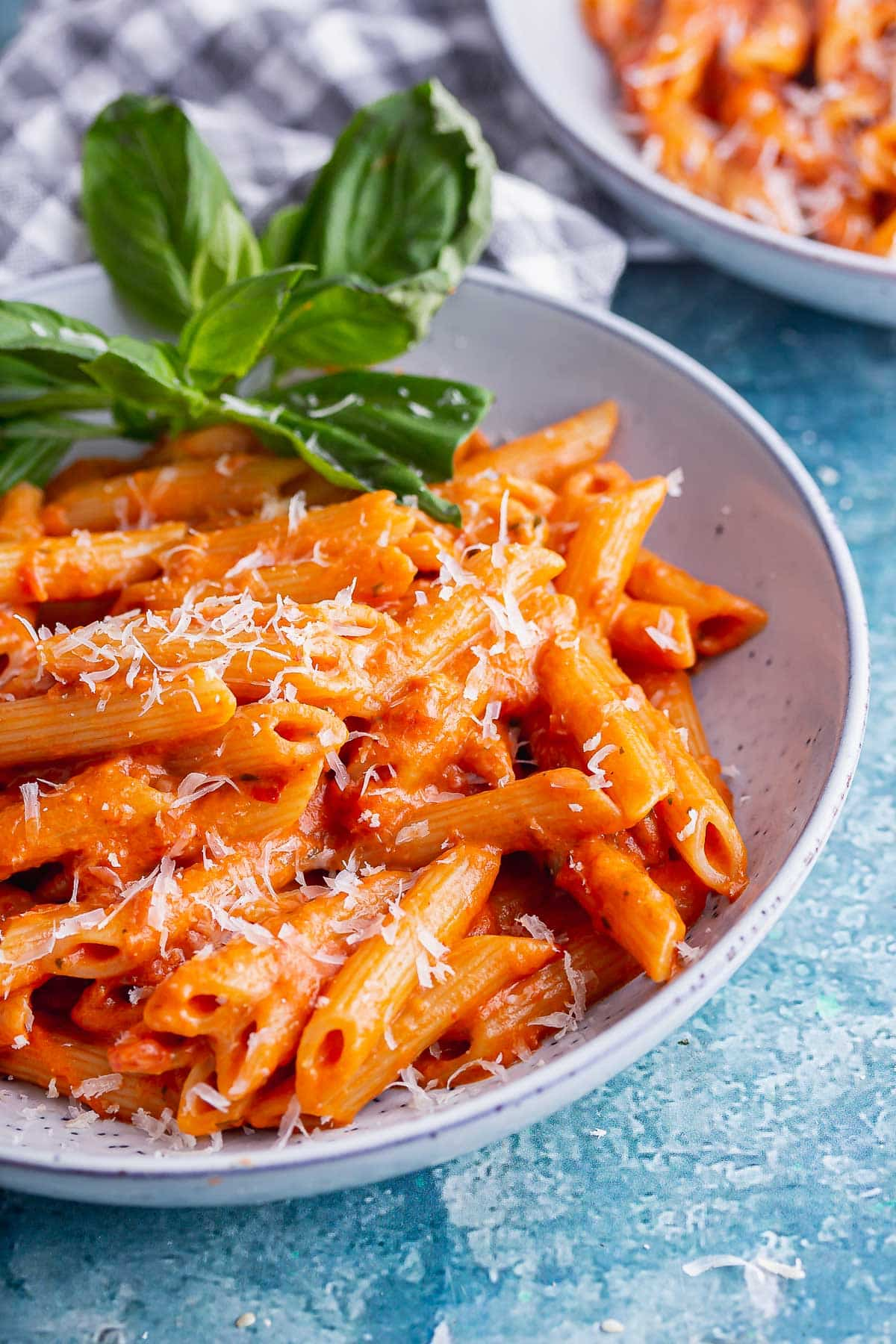 Close up of creamy tomato pasta in a blue bowl