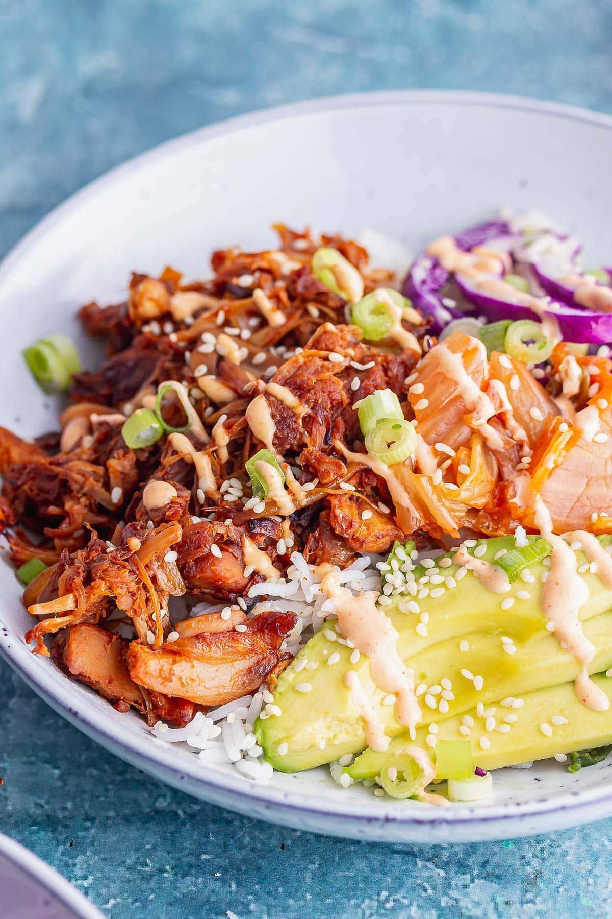 Side on shot of kimchi and jackfruit bowls with avocado