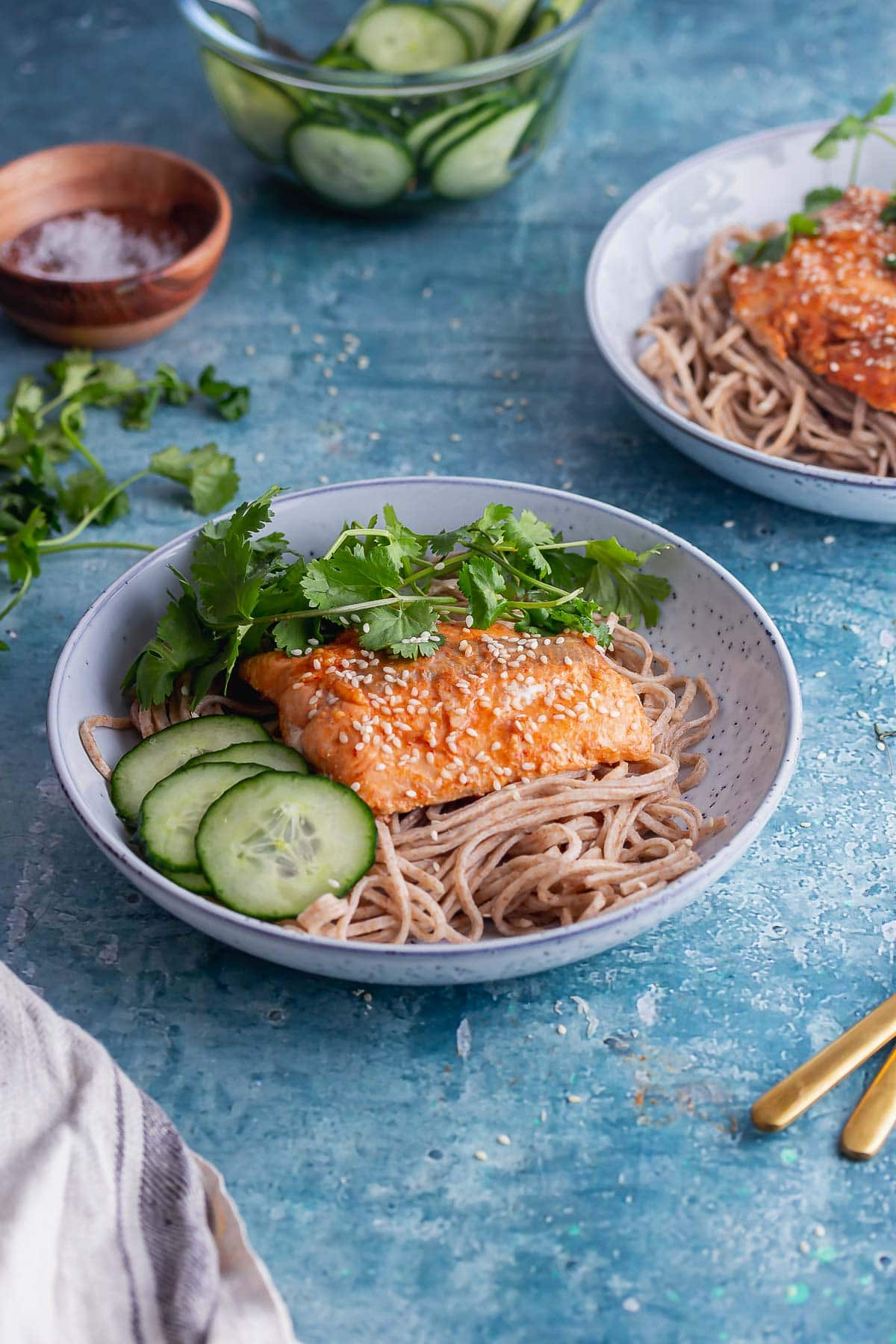 Blue bowl of honey soy salmon with noodles and cucumber