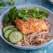 Honey roasted salmon with pickled cucumber and coriander on a blue surface