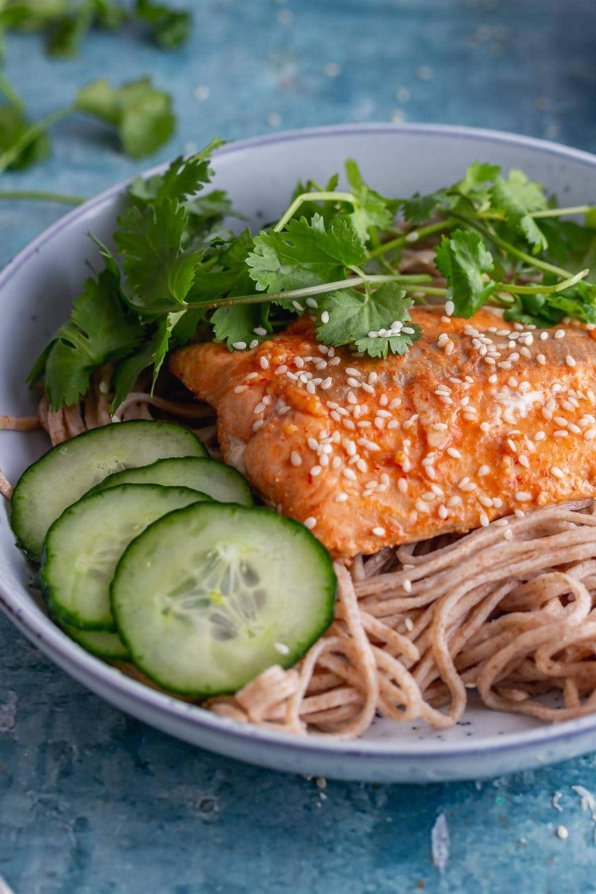 Bowl of noodles and glazed salmon on a blue surface
