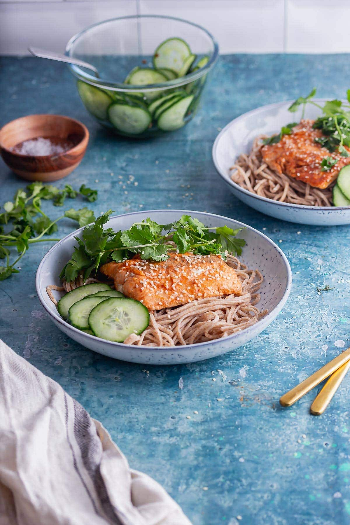 Blue bowl of noodles and salmon with cucumber