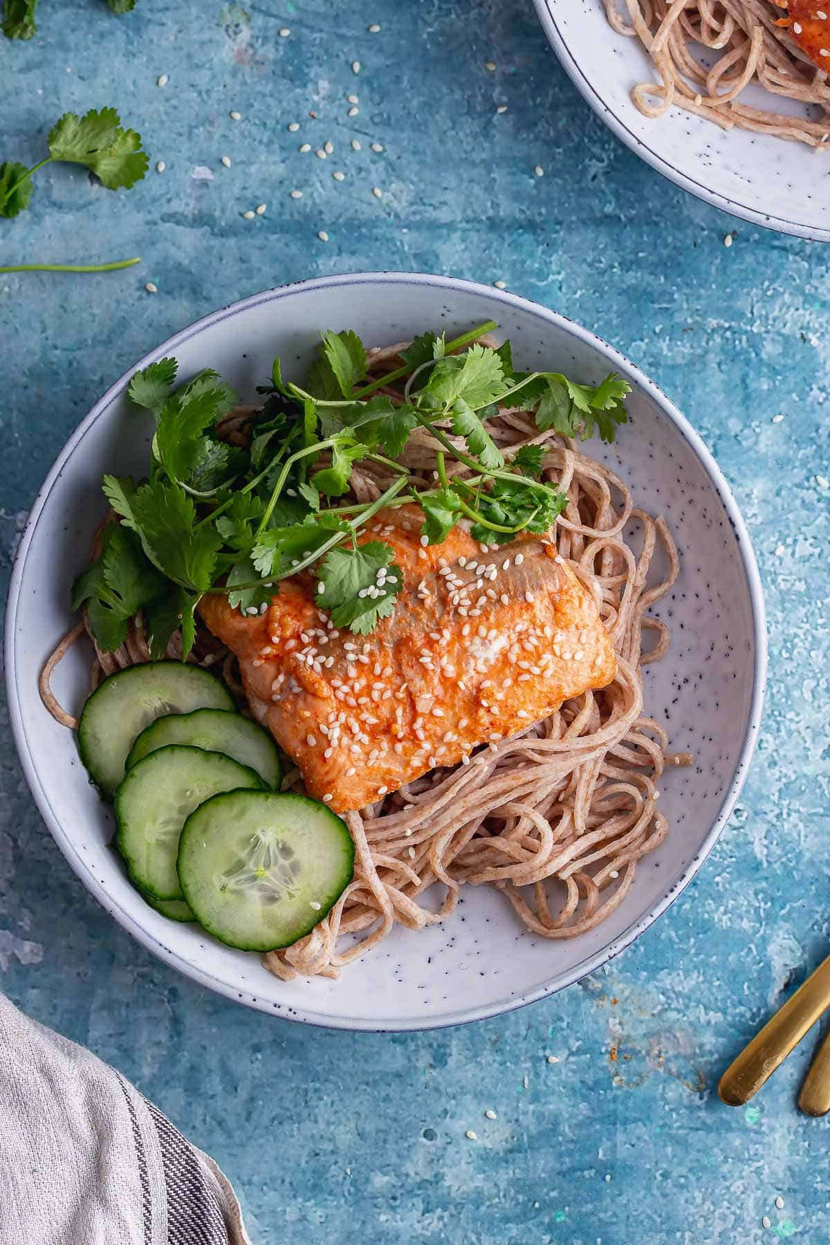 Overhead shot of salmon noodles in a blue bowl with coriander and cucumber