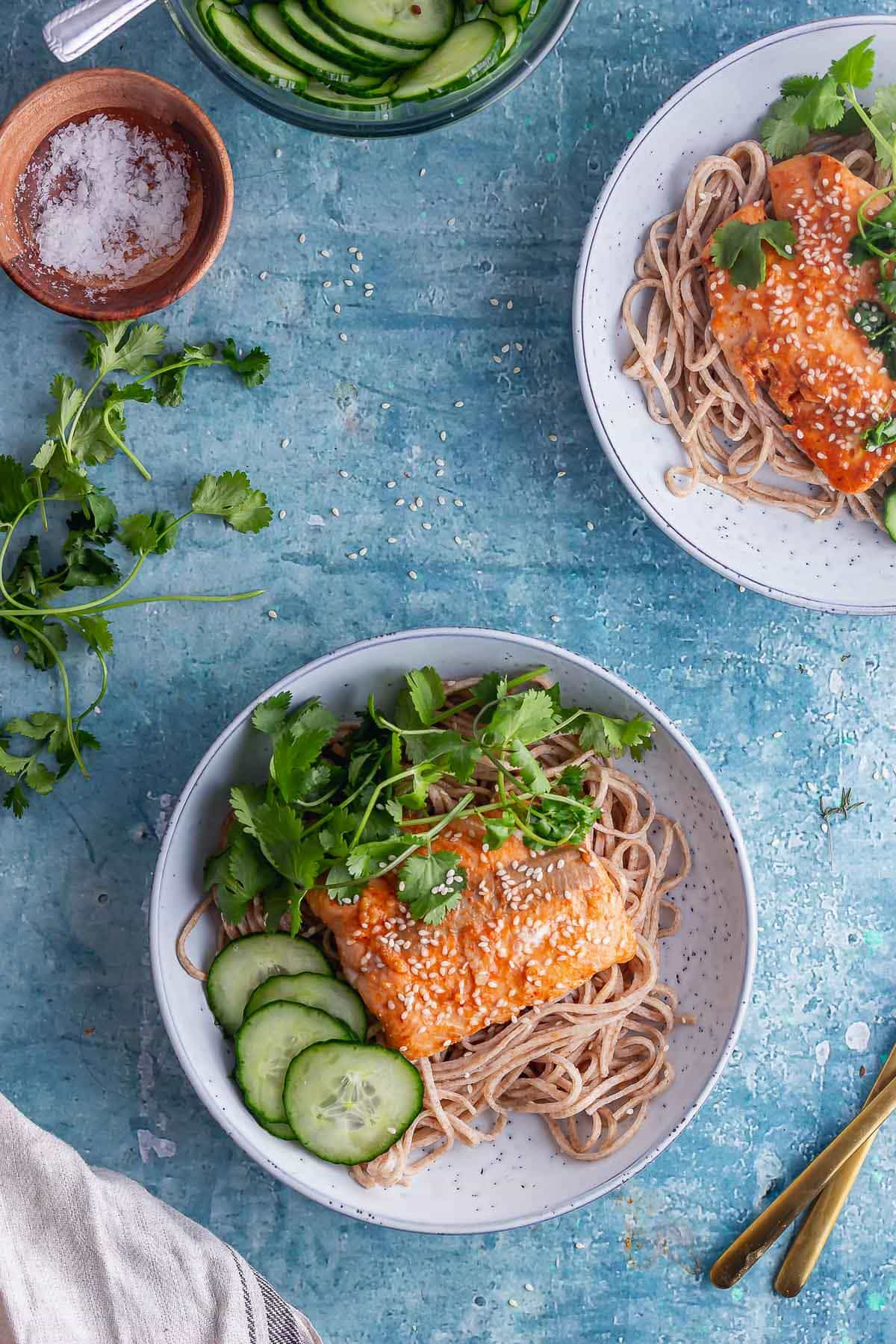 Overhead shot of honey soy salmon with cucumber and noodles