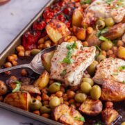 Sheet pan of cod and vegetables with a spoon