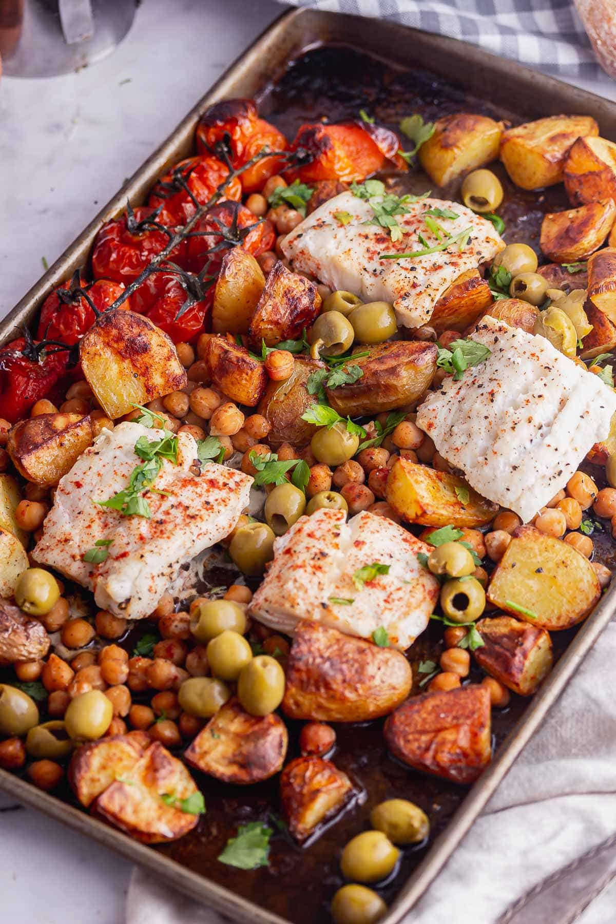 Overhead shot of baked cod and chickpeas on a marble background