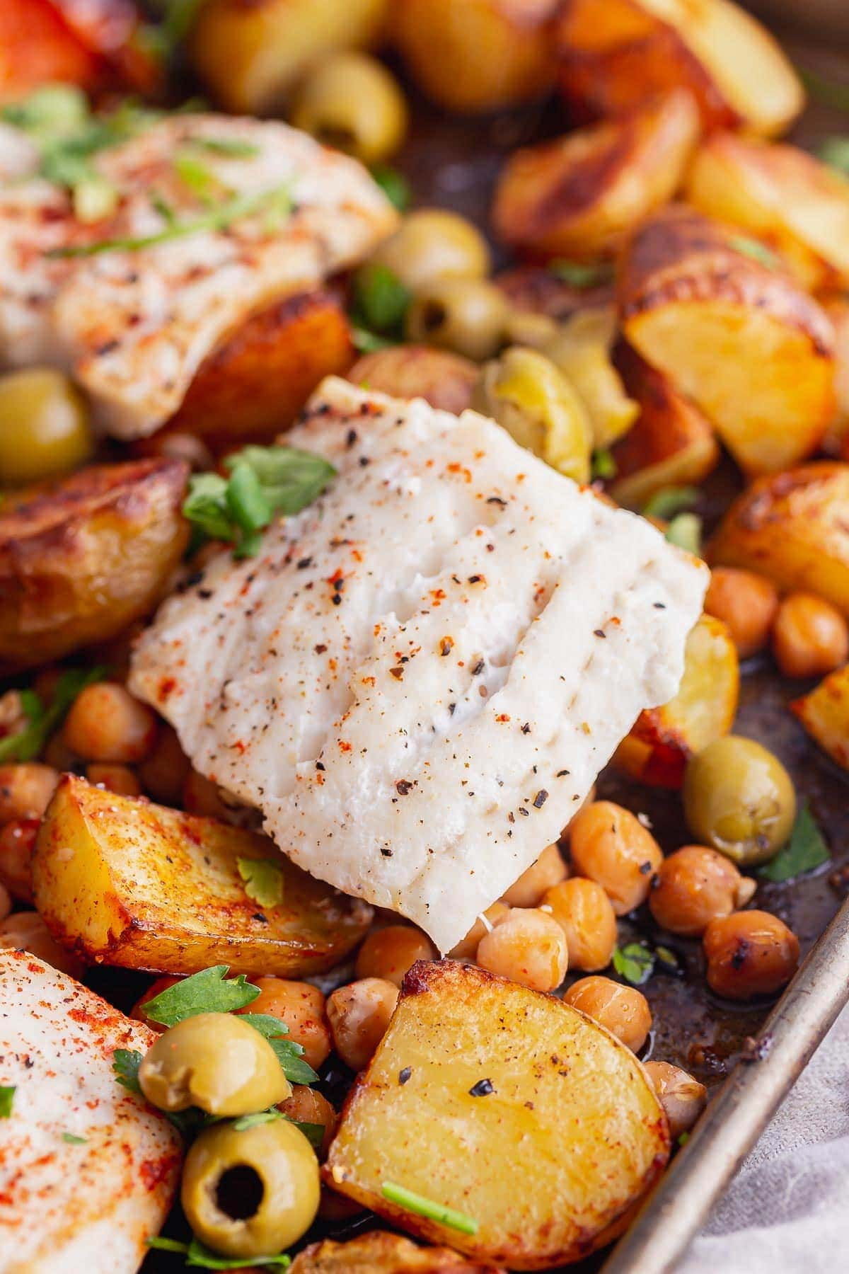 Close up of baked cod with vegetables on a tray