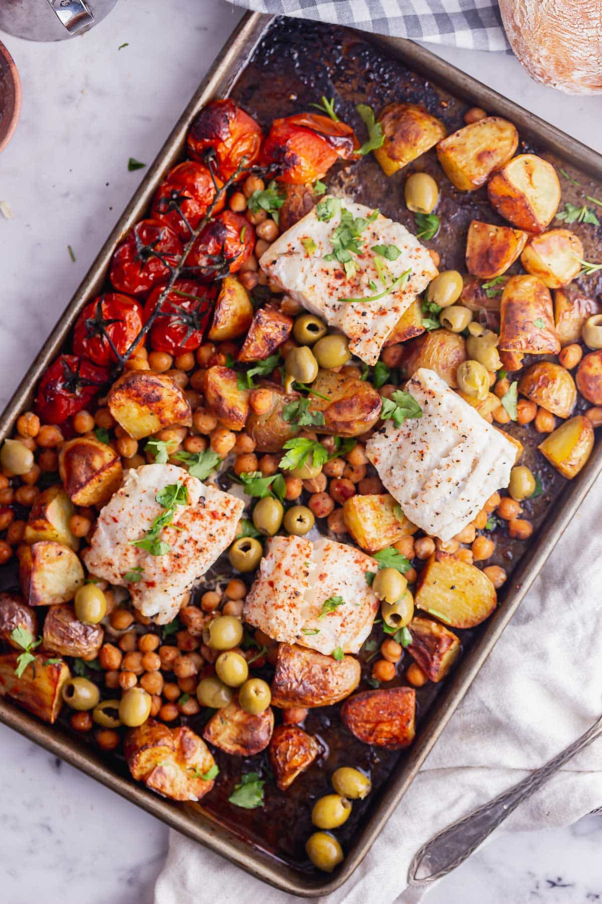 Overhead shot of cod and vegetables on a sheet pan