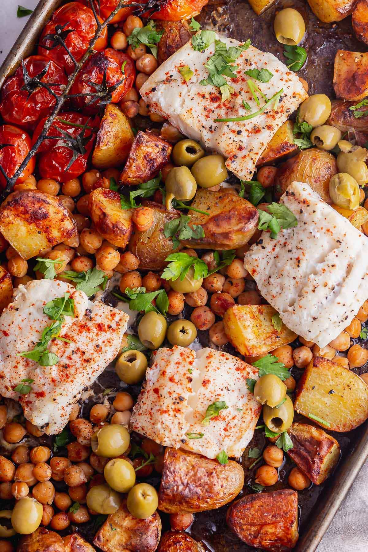 Overhead shot of cod pieces on top of potatoes and chickpeas