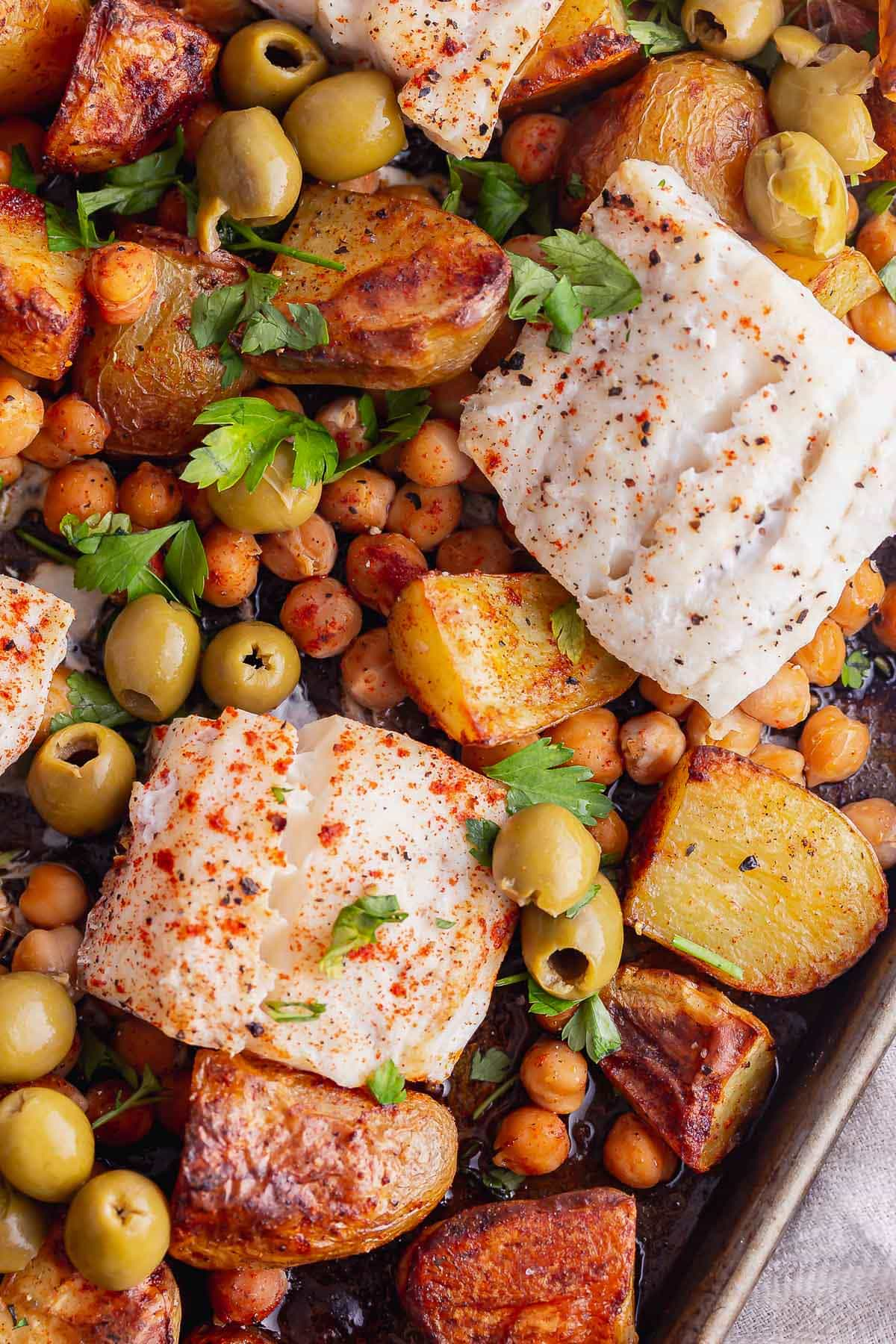 Close up of baked fish with chickpea and olives