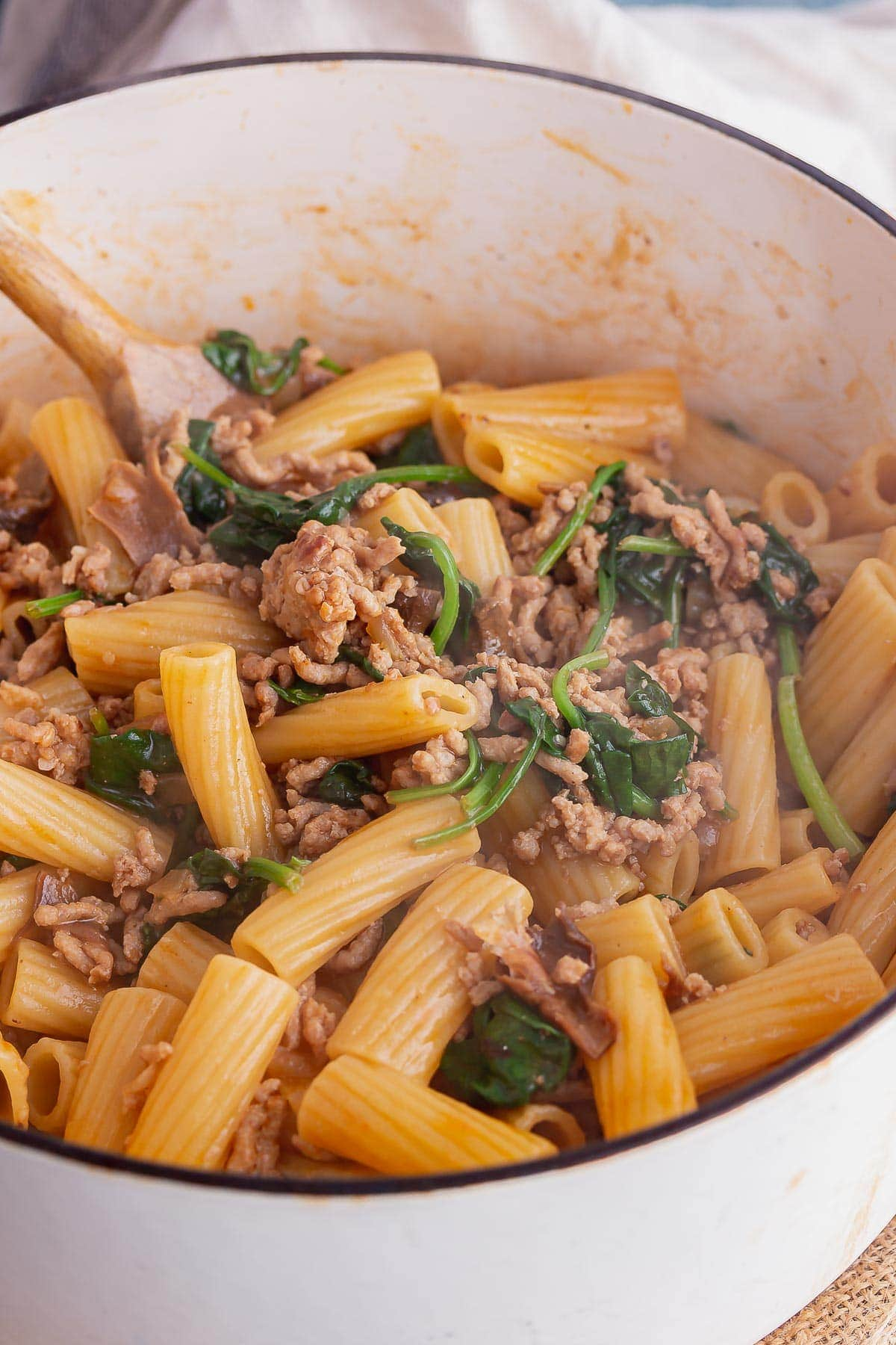 White pot of pork mince pasta with spinach