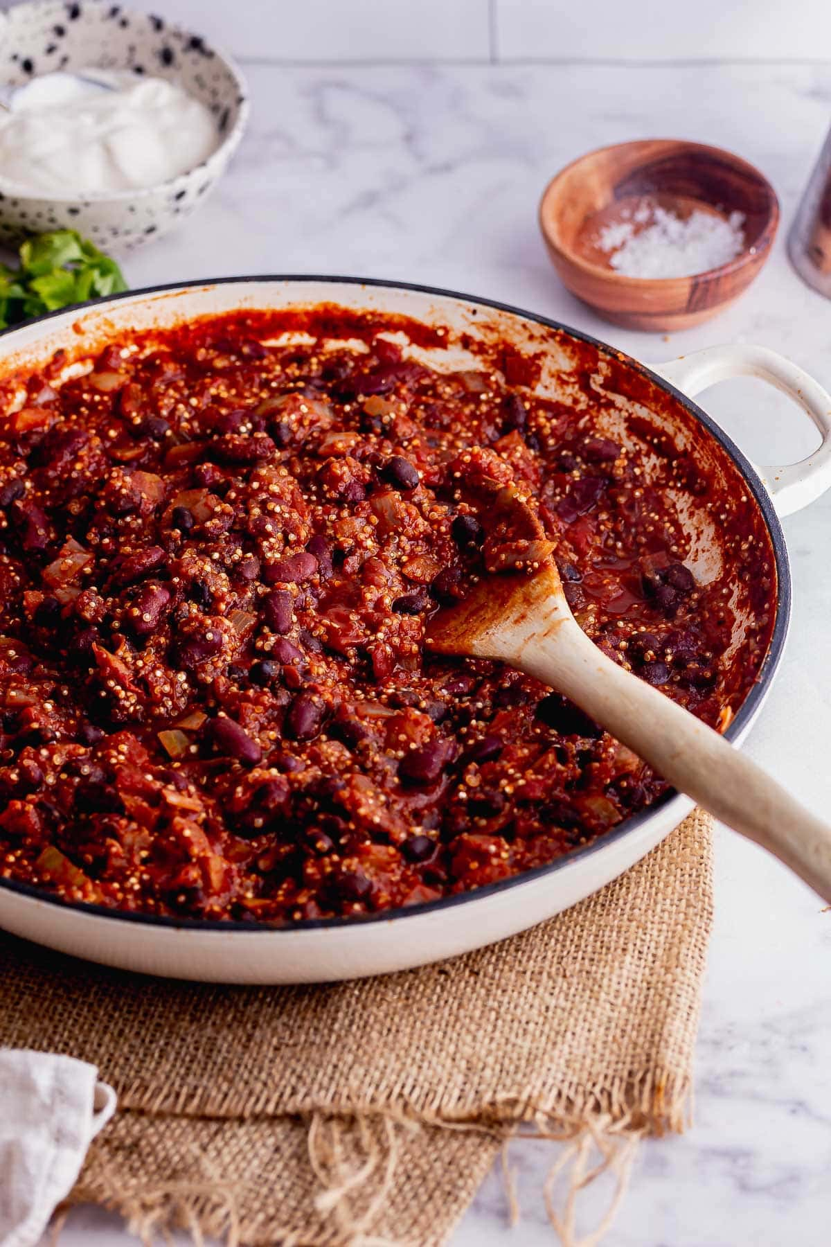 White casserole dish of vegan chilli with a wooden spoon