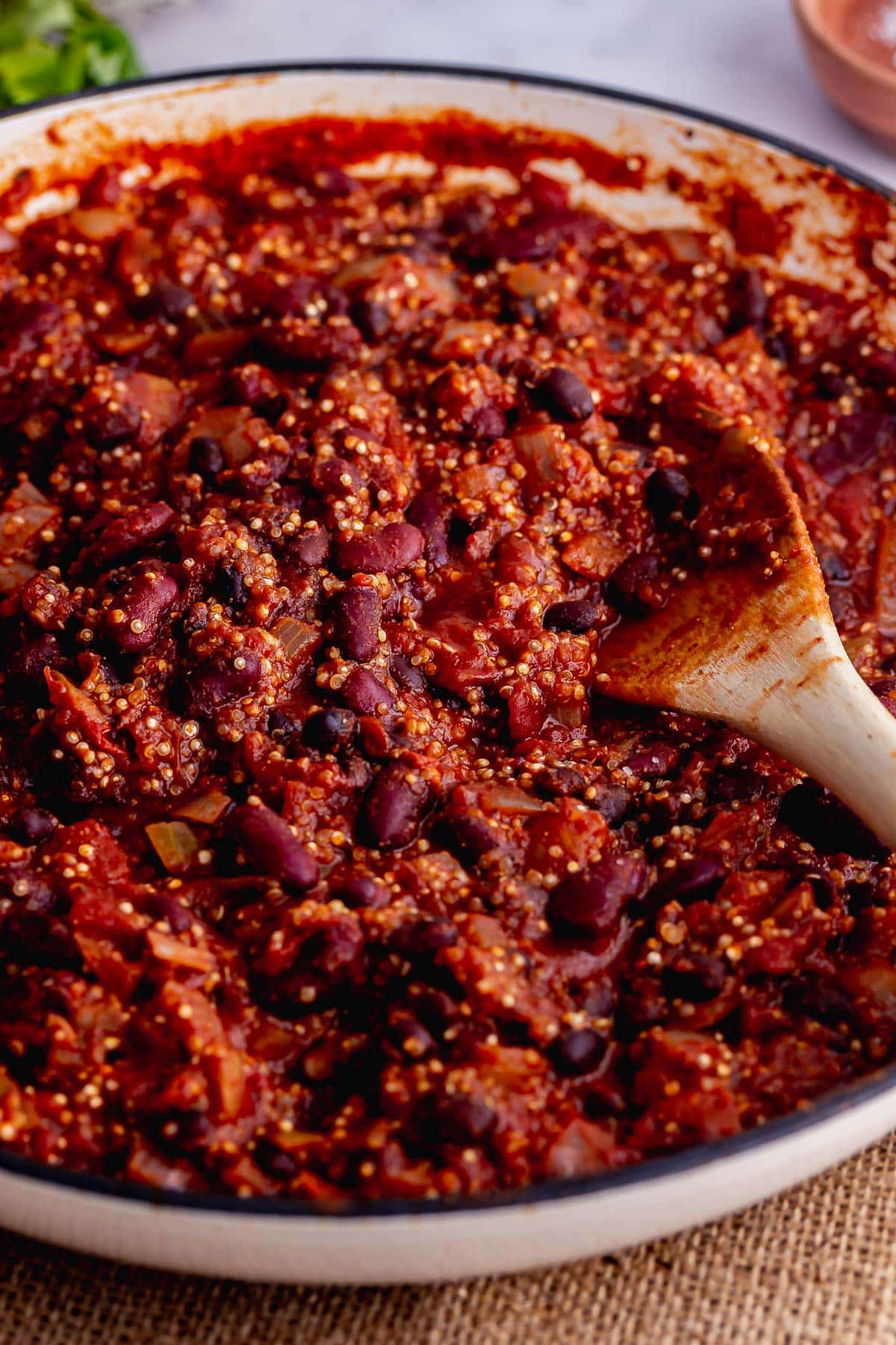 Pot of quinoa chilli with a wooden spoon on a mat