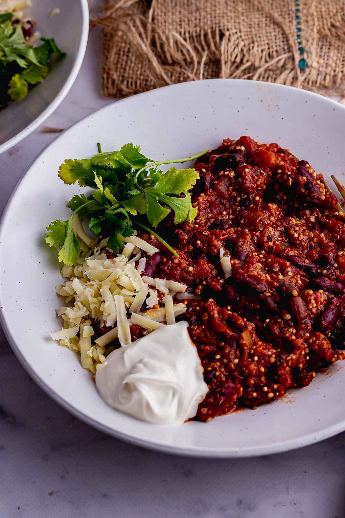 White bowl of quinoa chilli with cheese and coriander