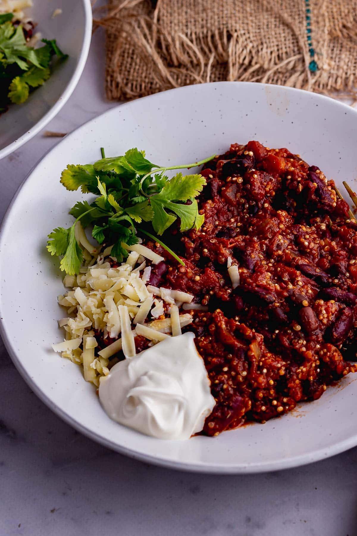 White bowl of quinoa chilli with cheese and coriander
