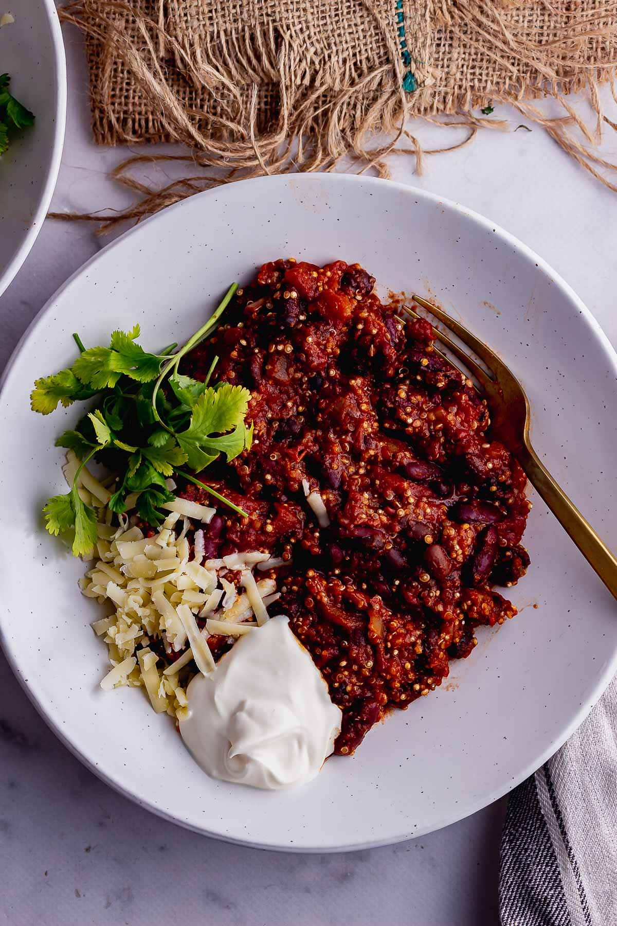 Overhead shot of quinoa chilli topped with cheese and creme friache