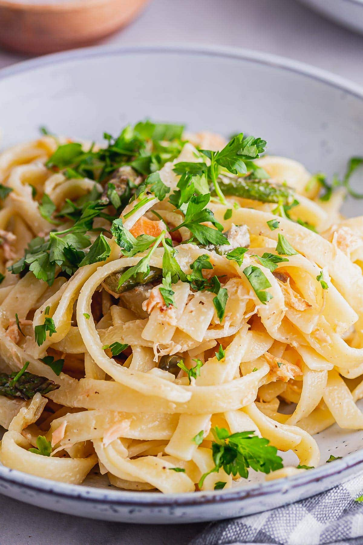Close up of pasta with smoked salmon topped with parsley