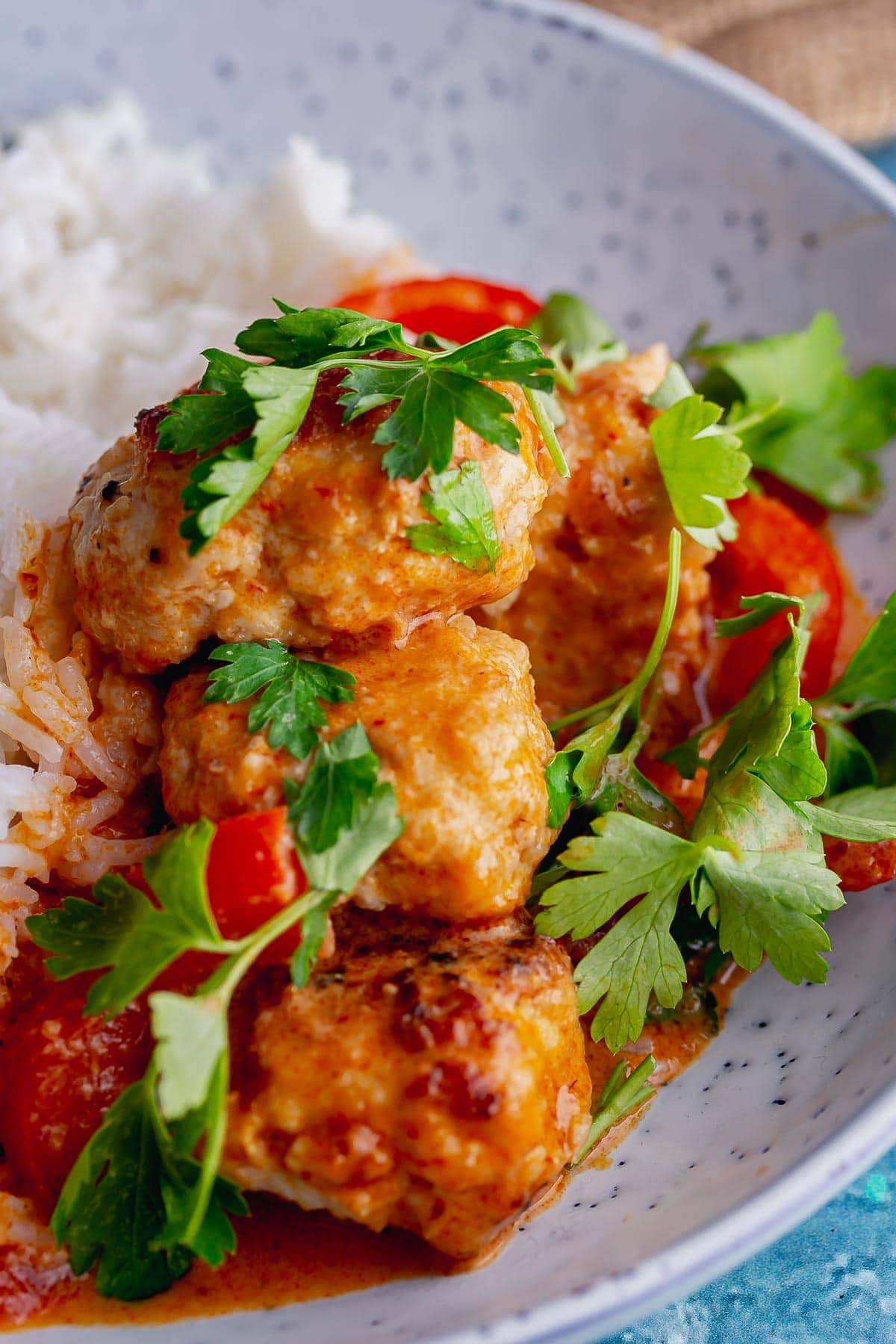 Close up of turkey meatballs in Thai curry sauce