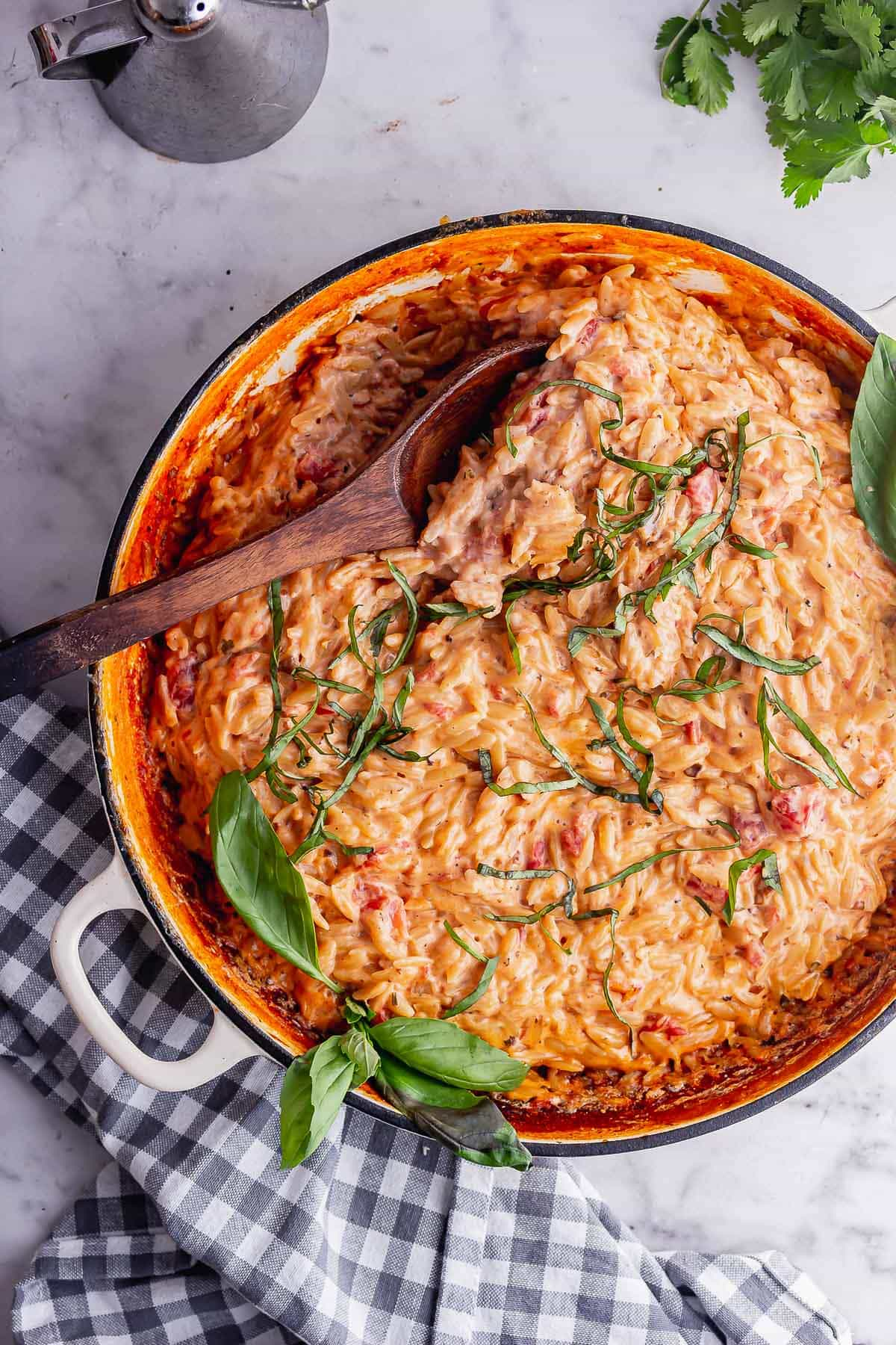 Overhead shot of tomato and mascarpone orzo with a wooden spoon