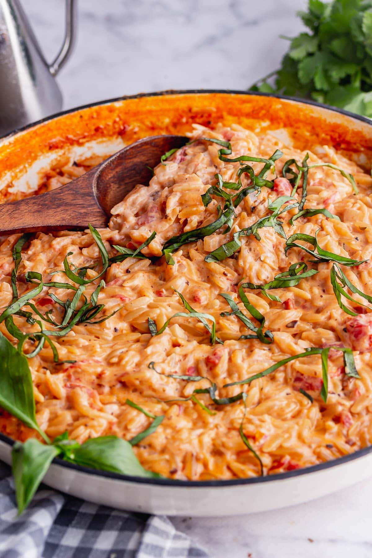 White pot of orzo risotto with a wooden spoon