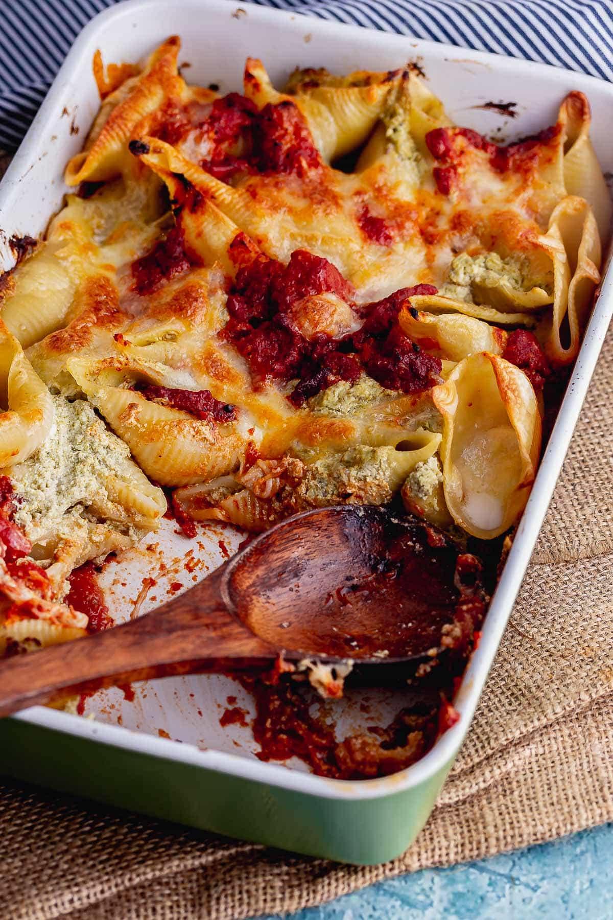 Pesto pasta bake with a wooden spoon