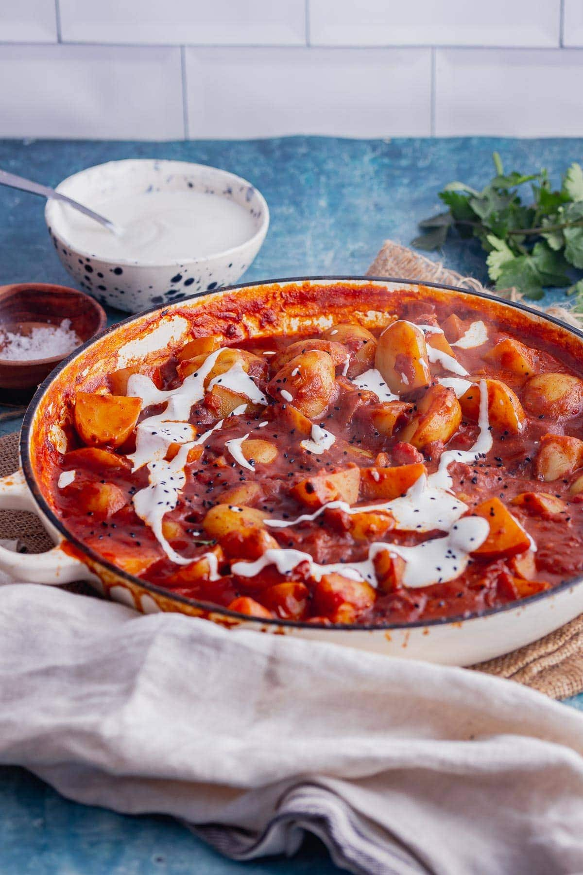 White dish of potato and tomato curry with yoghurt drizzle