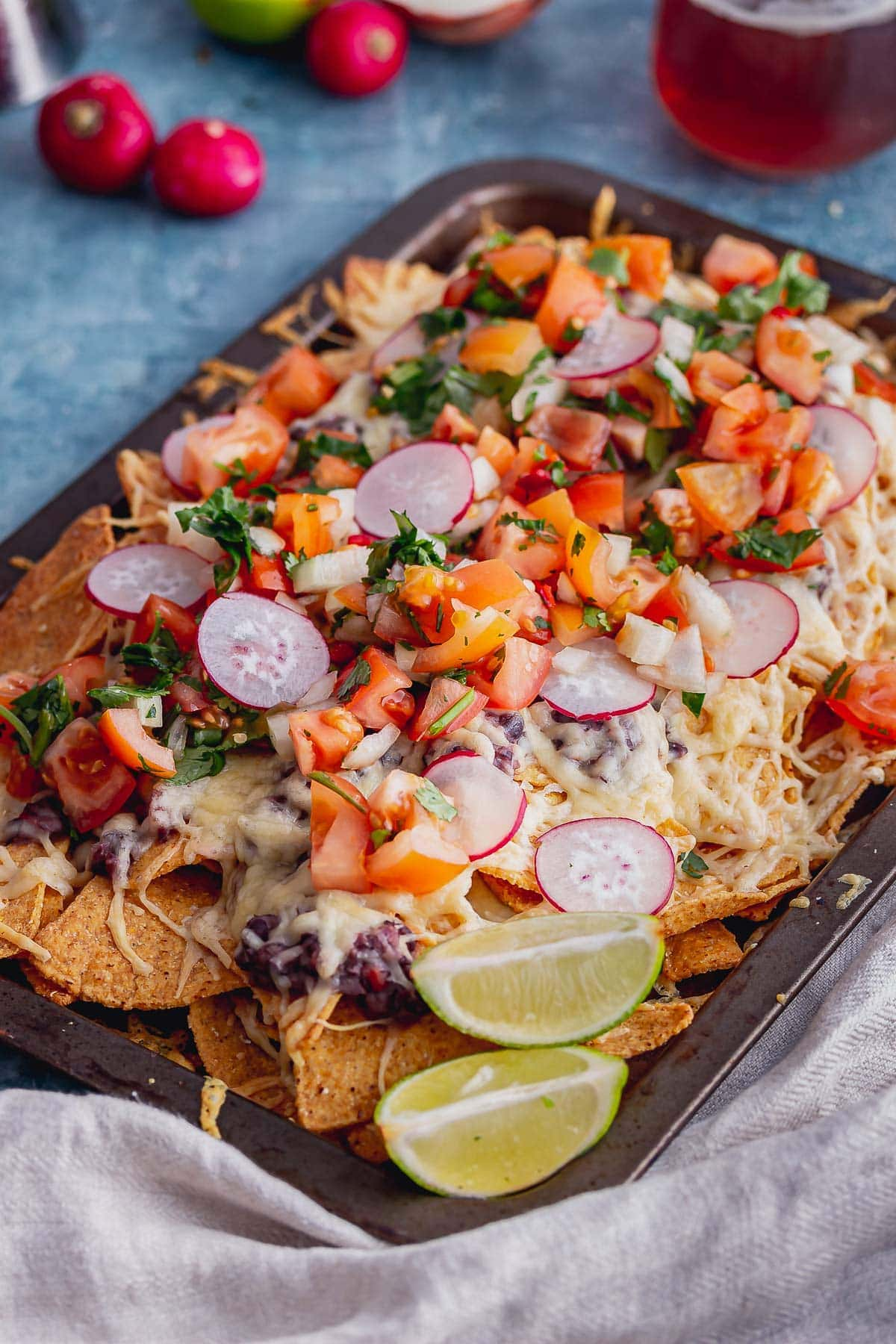 Tray of veggie nachos with lime wedges