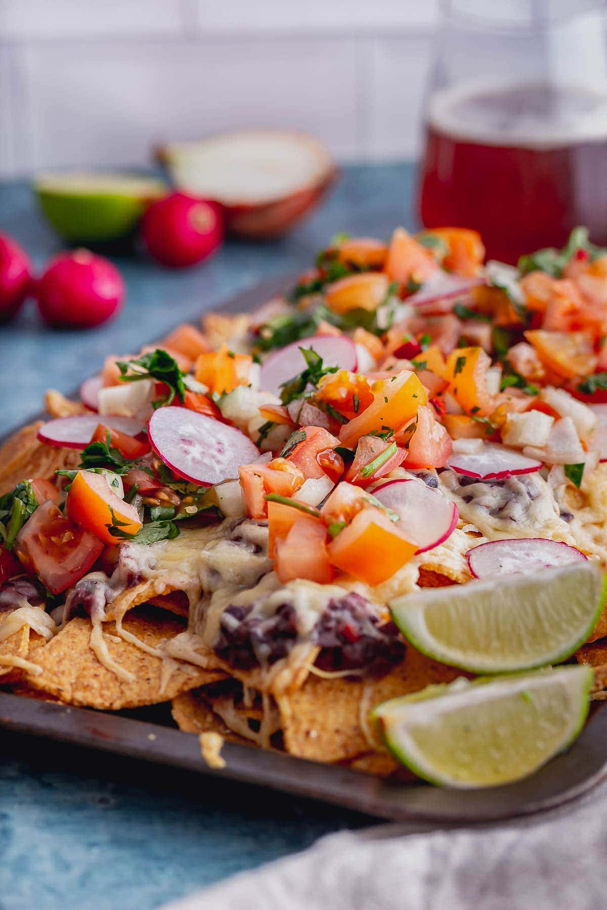 Veggie nachos on a baking sheet with lime wedges