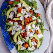 Overhead shot of butternut squash salad with avocado on a marble background