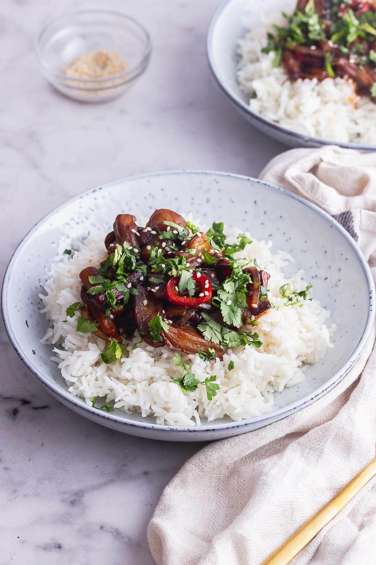 Blue bowl of stir fried aubergine on a marble background