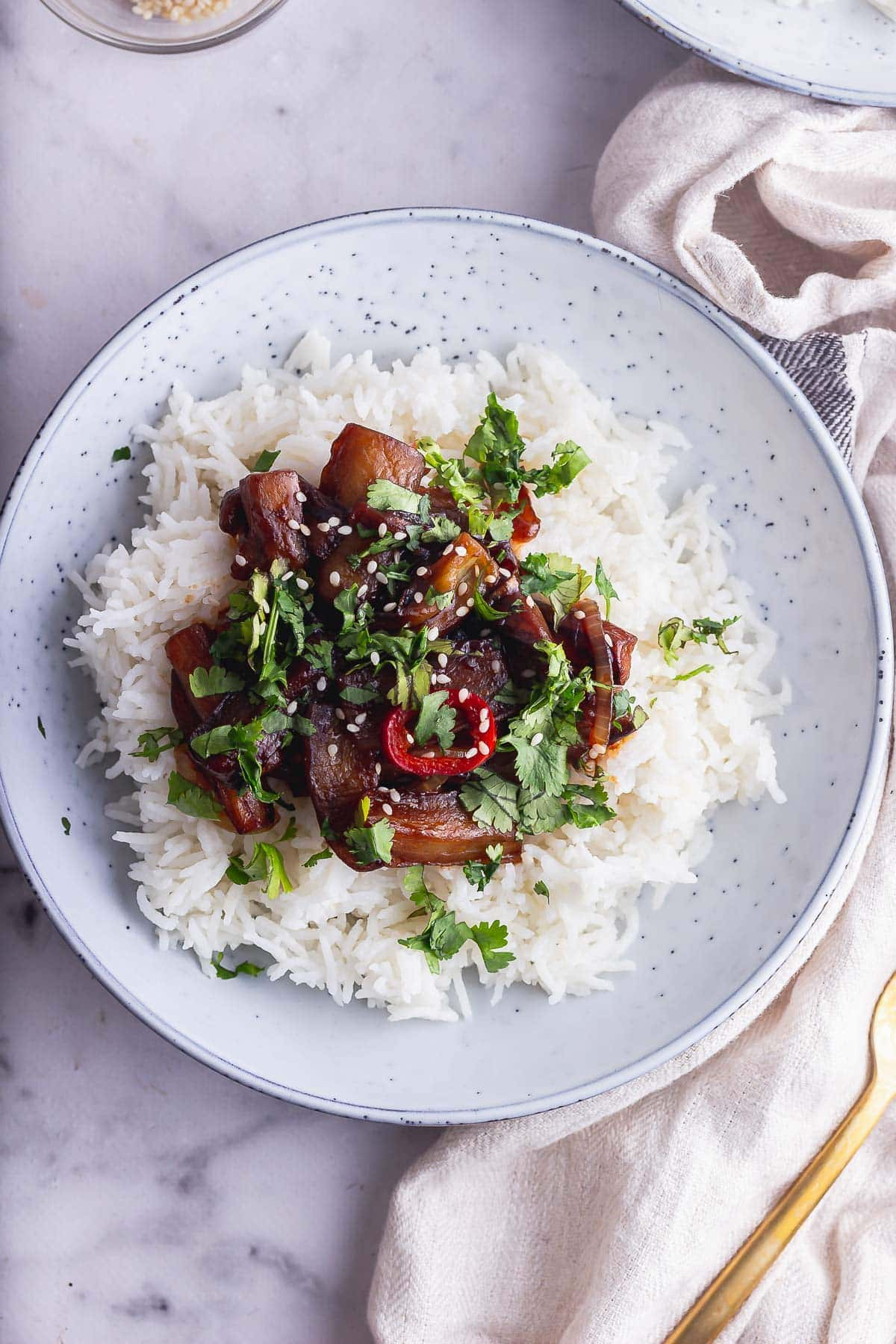 Overhead shot of spicy fried aubergine and rice on a marble background