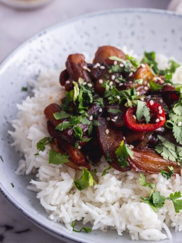 Close up of aubergine stir fry with rice in a blue bowl