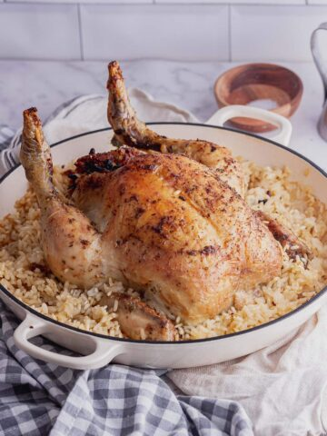 White dish of stuffed chicken risotto on a checked cloth