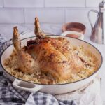 White dish of stuffed chicken and risotto on a checked cloth