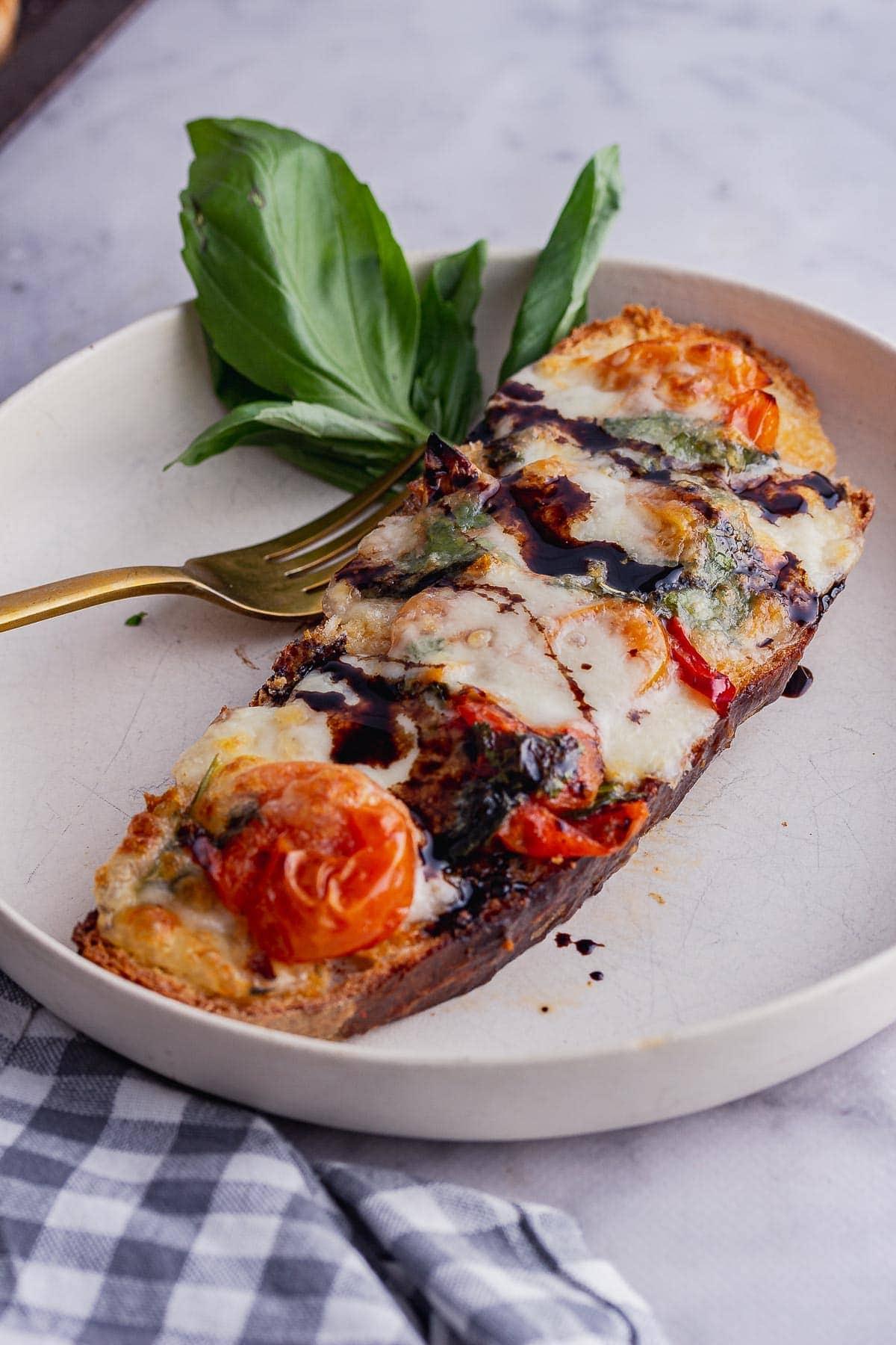 White bowl with tomato and mozzarella toast and basil