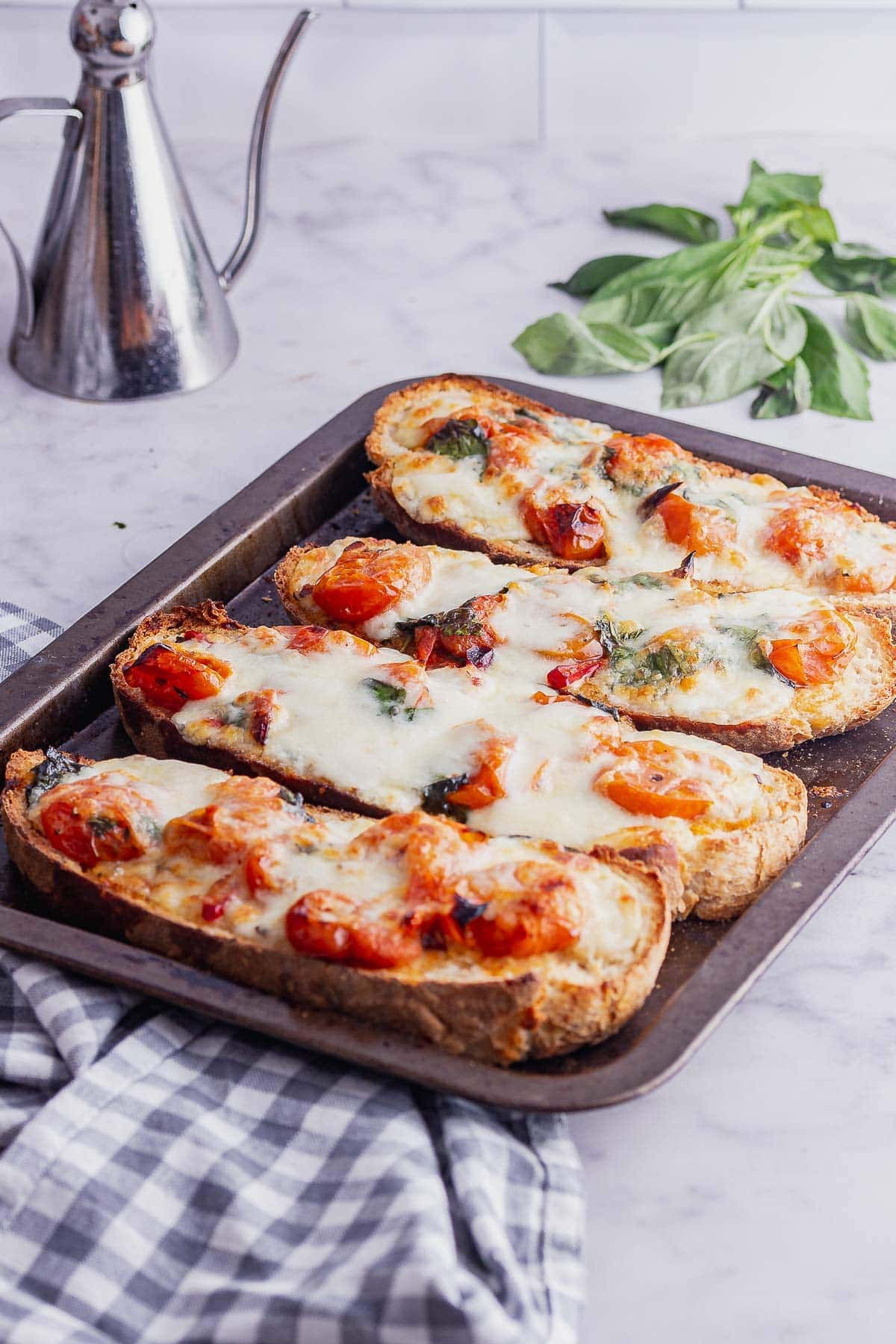 Tray of tomato toasts with mozzarella and basil on a marble surface