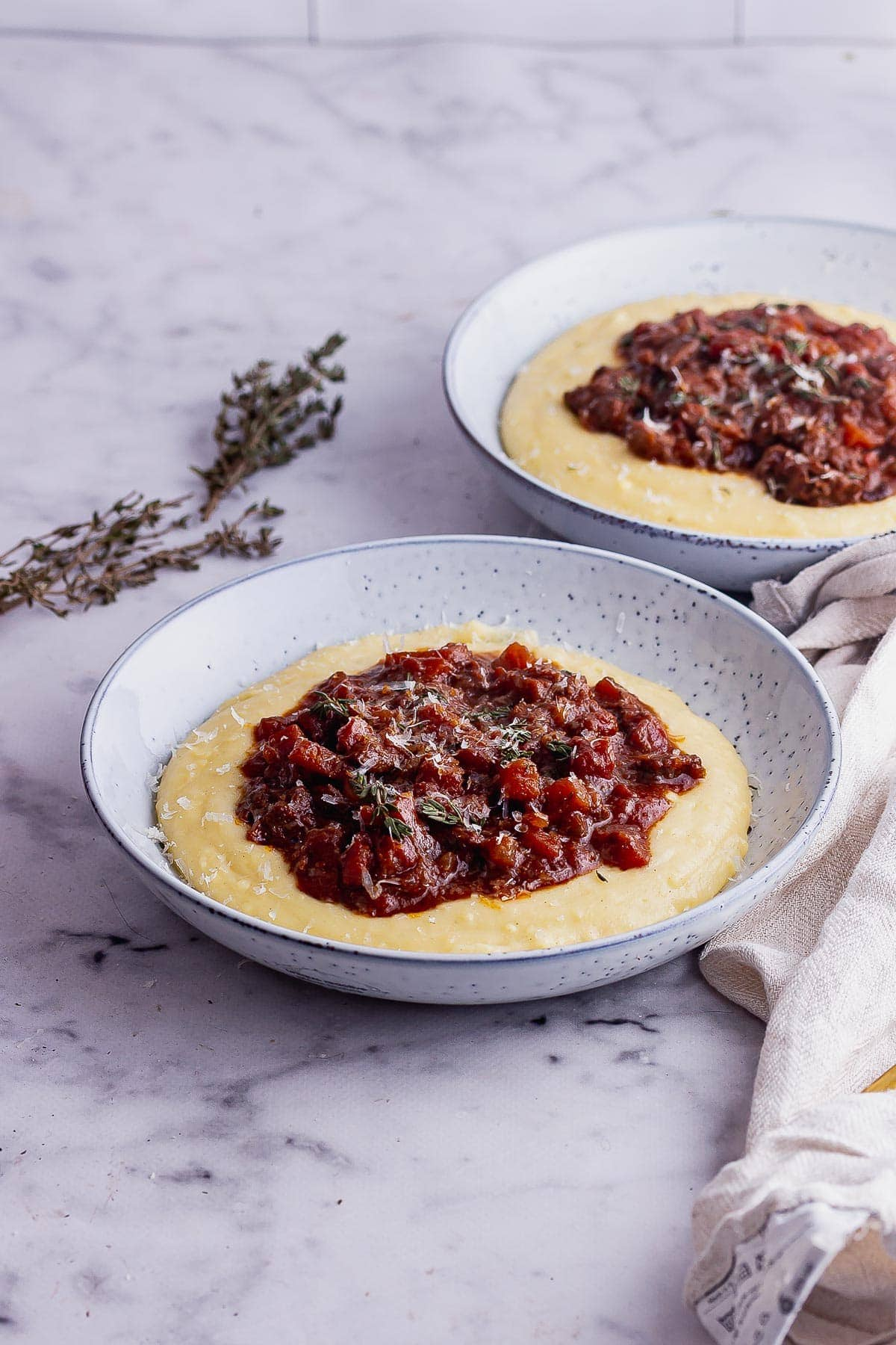 Bowls of polenta topped with rich beef ragout on a marble surface