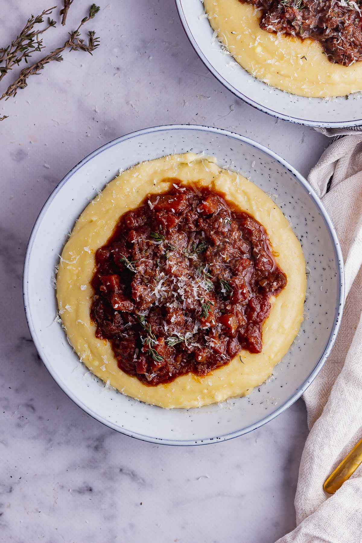 Overhead shot of a blue bowl of polenta and ragu on a marble background