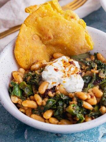 Close up of bean and pearl barley stew with roti in a white bowl