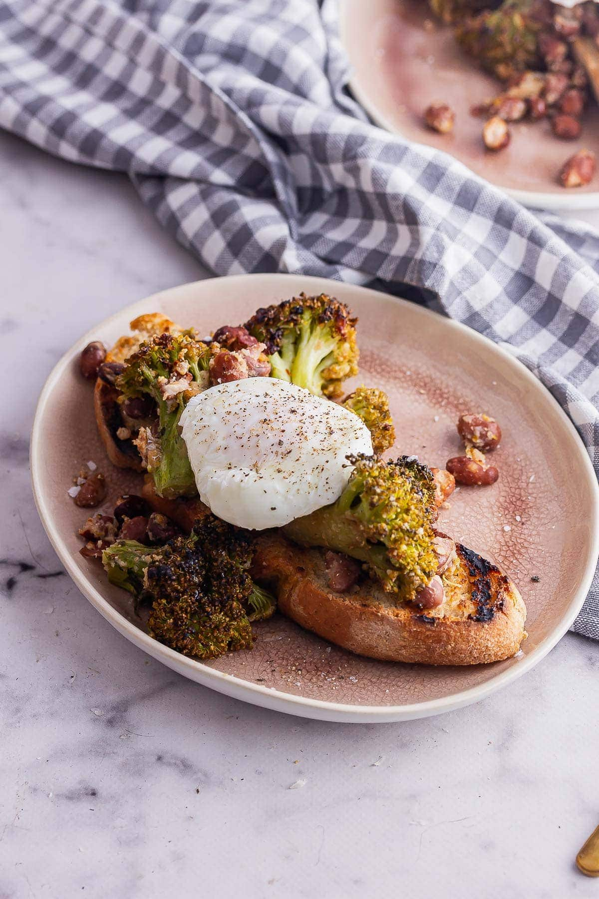 Pink plate of roasted broccoli toast with a poached egg