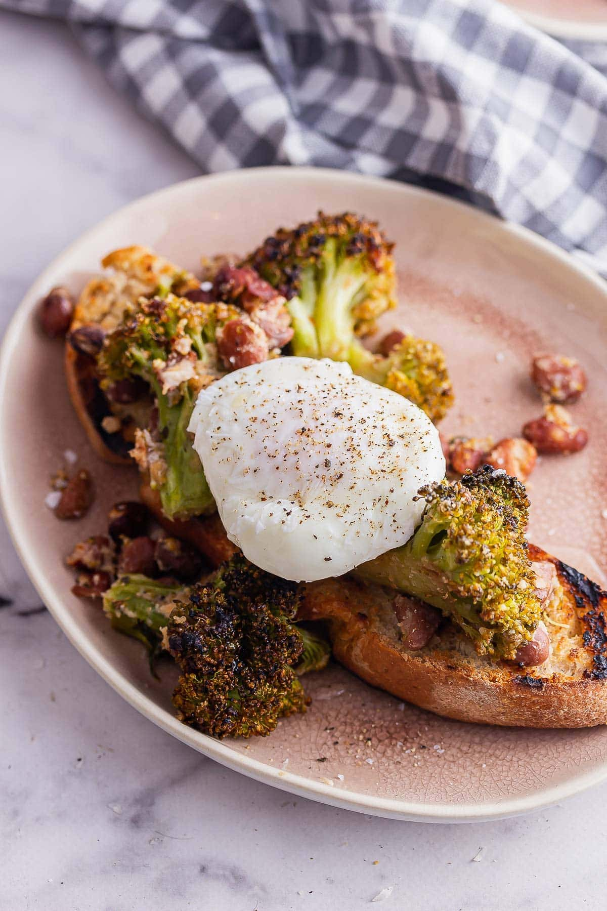 Pink plate of toast with broccoli and a poached egg