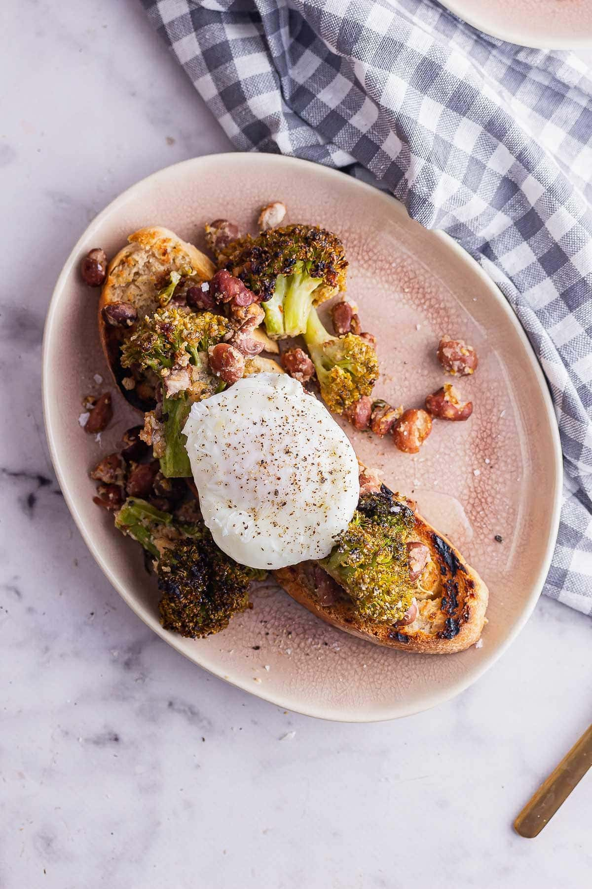 Overhead shot of roasted broccoli with beans on toast on a marble surface